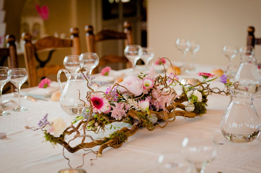 photo d'une table décorée par une composition végétale et florale dans les tons tendres